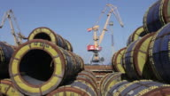 Slow zoom in on sections of large pipe, stacked at Odessa's docks.