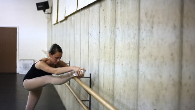Slow zoom out of a ballet dancer stretching on the barre.