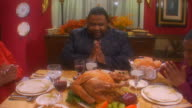 Slow zoom out on a man praying before eating a Thanksgiving meal