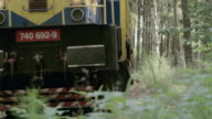 SELECTIVE FOCUS A slowly approaching freight train traveling down a narrow track in the countryside