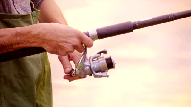 Slow-Mo:Fisherman pulls the fishing line on reel