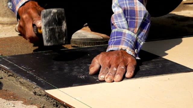 slow-motion, construction worker using hammer tiling floor