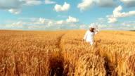 Slow-motion: Crane Shot Of Young Woman Walking In Wheat Field