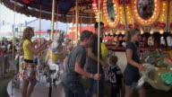 Slow-motion footage of four young adults walking up to carousel