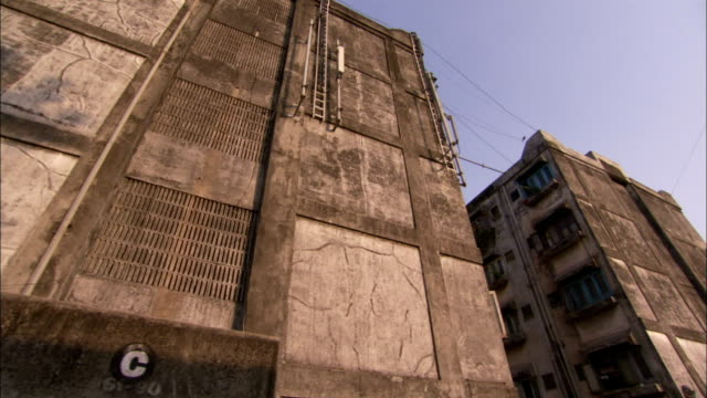 Slum residents stand outside their dilapidated apartment buildings. Available in HD.