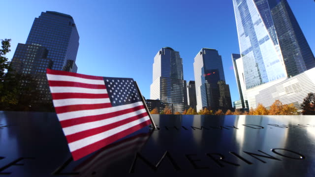 A small American flag waving by winds at 9/11 Memorial which is surrounded by autumnal trees and skyscrapers.