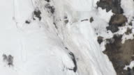 A small avalanche sends chunks of ice and snow cascading over a high, sheer cliff.