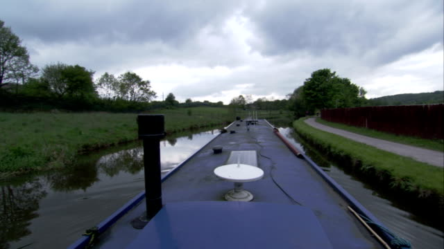 A small barge floats down a canal in the countryside. Available in HD.
