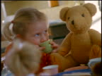 Small blonde girl drinking from teacup at tea party with dolls + teddy bear