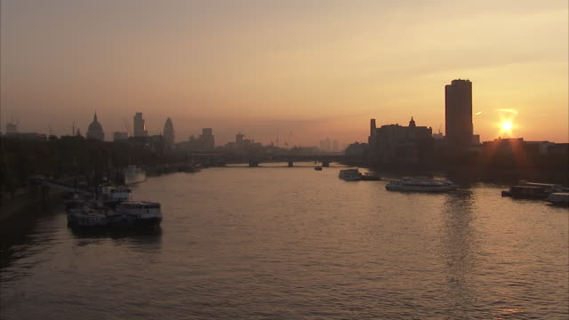 A small boat floats near Canary Wharf on the River Thames at sunset Available in HD.