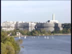 Small boats sail before Watergate complex on Potomac River Washington Monument in background Washington D.C.