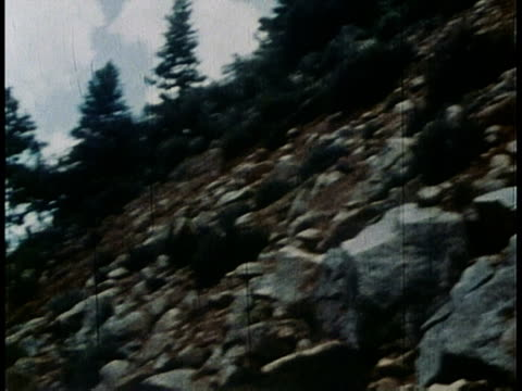 1978 PAN small boulder rolling down rocky hillside onto road / United States