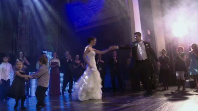 small boy and girl dance together as bride and groom dance on stage