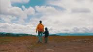 Kleiner Junge und seine Mutter die Berg-Wanderweg an bewölkten Tag