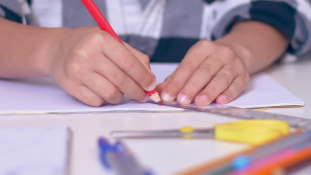 Small boy drawing lines using ruler in a notebook