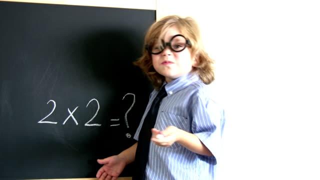 Small boy in front of blackboard