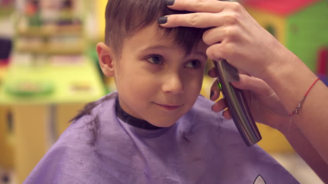 Small boy is cut his hair by hairdresser