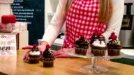 Small business owner in cake shop serving cupcakes