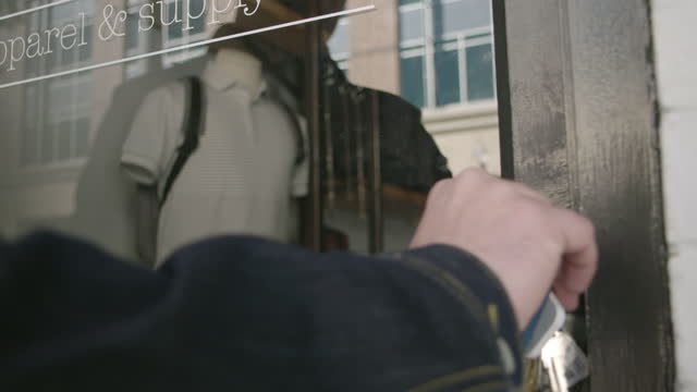 CU. Small business owner unlocks door to downtown clothing store and walks inside.