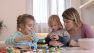 Kleine Kinder und ihre Mutter mit Rätseln zu Hause spielen.
