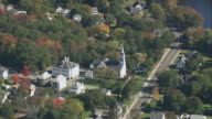 AERIAL Small city with church spire, public buildings, and lots of trees, some with autumn foliage / Massachusetts, United States