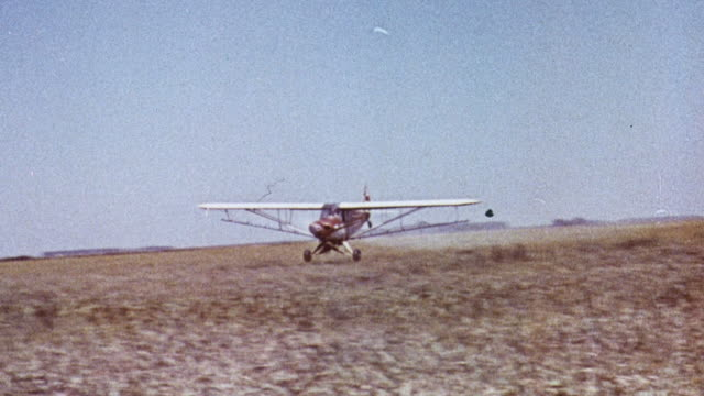 1965 MONTAGE Small crop-dusting airplane flying low to the ground over field of grain / United Kingdom