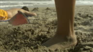 SLO MO small foot kicking in sandcastle, Spain