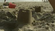 SLO MO small foot runs through sandcastle, Spain