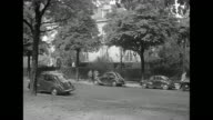 LS small group of people stand in front of hedge of mansion on treelined street with several cars parked on it / CU group of reporters and...