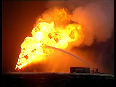Small hose of water hitting large flames. Gulf War: Kuwait, 1991.