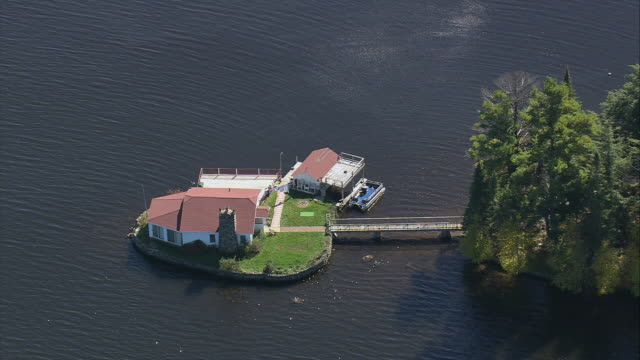AERIAL Small island with house and boathouse on lake with connecting bridge / Massachusetts, United States