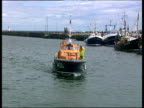 Small lifeboat travelling into harbour man stands on front of boat in waterproof gear with life jacket he uses pole to guide the boat to the quay side.