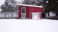 Small modern tiny home exterior during snowstorm.