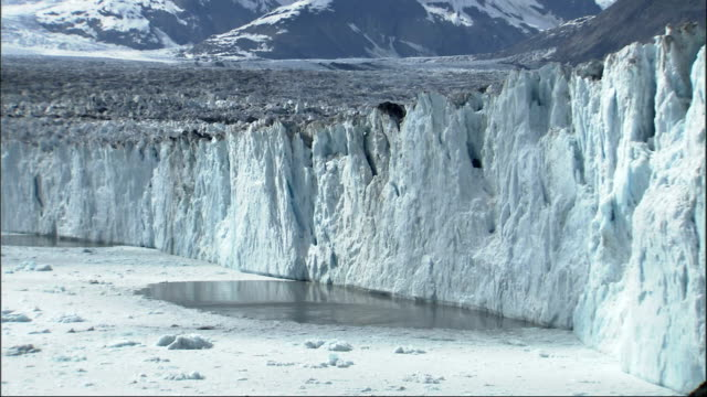 A small piece of the Columbia Glacier breaks off and splashes in the ocean. Available in HD.