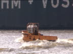Small pilot boat sails along wall of dry dock tilt up to large container ship Hamburg