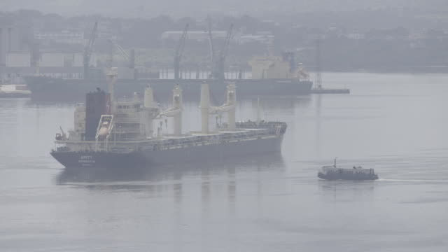 Small ship sails past large cargo ship in port of Havana