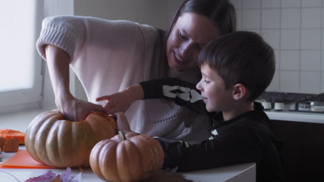 Small son helping mother to make pumpkin for halloween