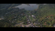 AERIAL ZI Small town on lake shore with wooden church / New England, USA