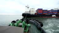Small tug boat assisting bulk cargo ship.