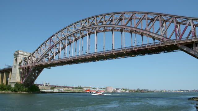 Small tugboat moves along the East River as Amtrak train crosses the Hell Gate Bridge above.
