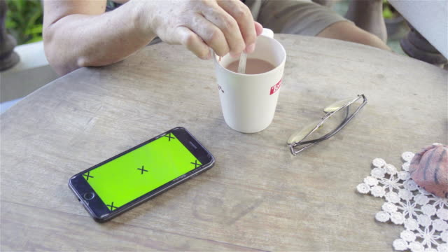 4K: Smart phone on table in morning.