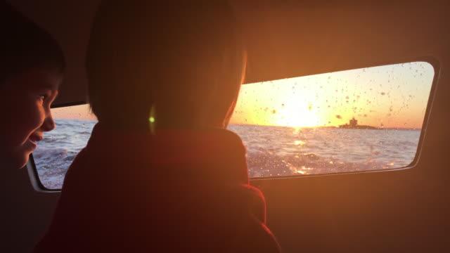 Smartphone-Video von zwei Kindern, die den Sonnenuntergang von der Boot-Kabine