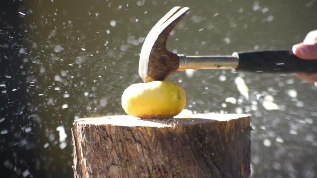 Smashing lemon with hammer slow motion