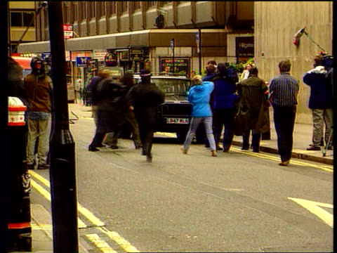 Smear allegations LIB ENGLAND EXT Jonathan Aitken from car LMS Photographers running forward to take picture of Aitken Photographers around Aitken...
