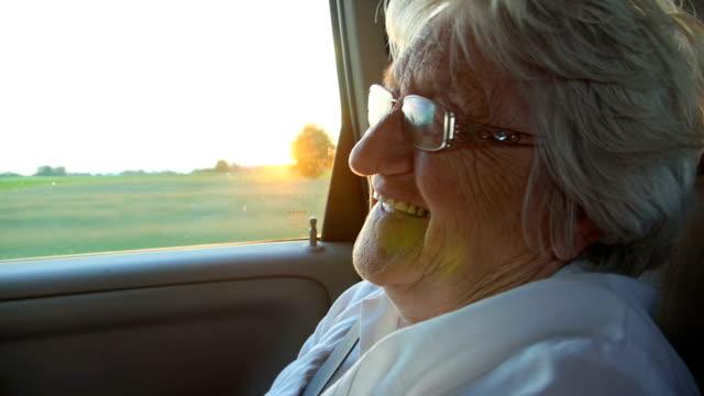 Smile senior women in the car at sunset