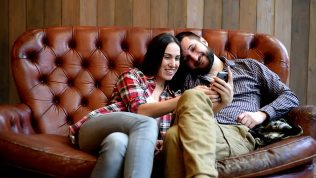 smiley young couple sitting on sofa and taking a selfie picture by the smartphone