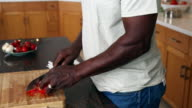 Smiling African American man chopping tomato in domestic kitchen