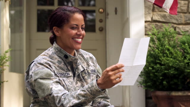 Smiling African American soldier reading letter on front stoop