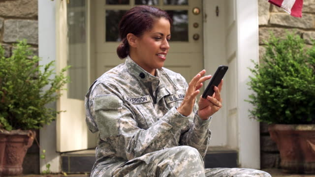 Smiling African American soldier texting on cell phone on front stoop