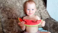 Smiling baby boy eating watermelon
